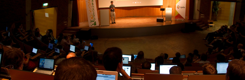 Photo of a talk at GUADEC 2010, with speaker talking and several attendees with laptops